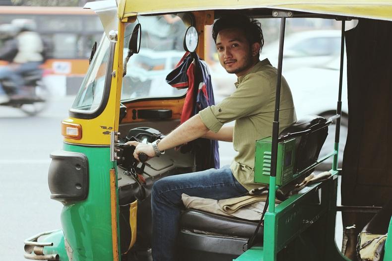 こっちを振り向いて笑うオートリキシャのドライバー