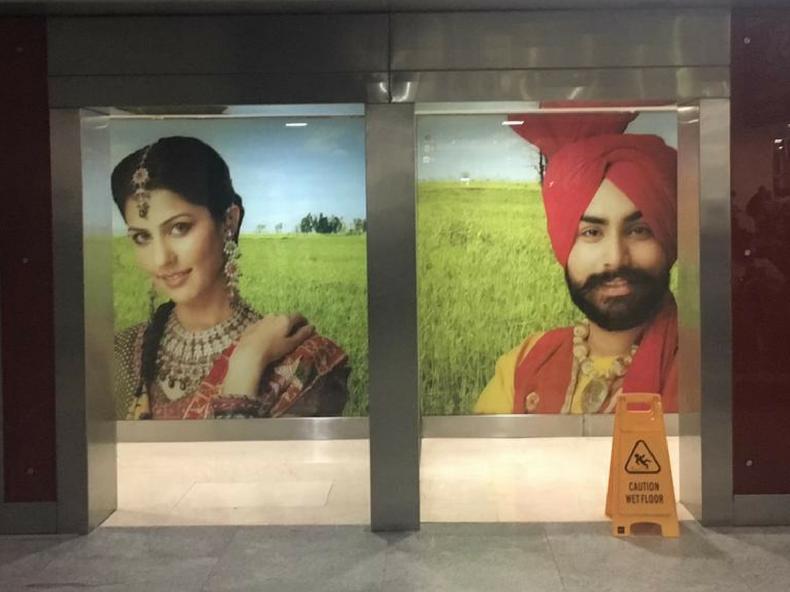 インドのデリーIGI空港のトイレの入り口。いかにもインドな男女の写真がでかでかと貼ってある。