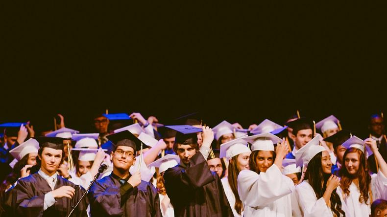 卒業式で帽子を投げようとする学生たち