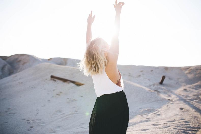 砂丘で太陽を浴び、両手を高く掲げる金髪女性の後ろ姿