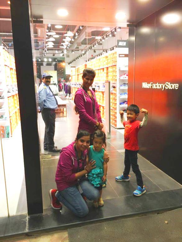 NIKEショップの前でインド人スタッフの女性2人と一緒に写真を撮る2人の子どもたち。