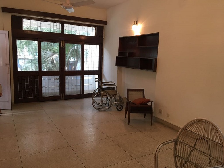 インドの家の広々としたリビング。タイルのフロアと窓、そして車椅子。