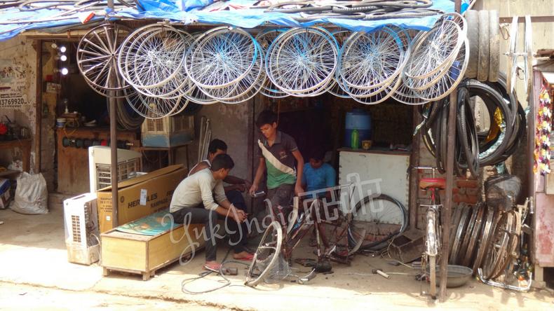 沢山の自転車のホイールが軒先にぶら下がったインドのローカルマーケットの自転車屋さん