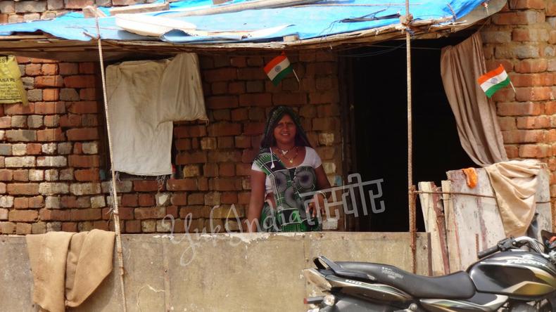 レンガの隙間に国旗を挿した家とインド人女性