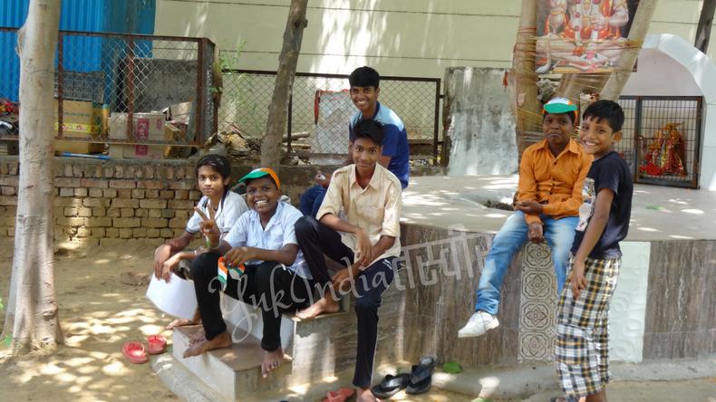 神様のいる木の根元で座り込んでいるインド人の男の子たち