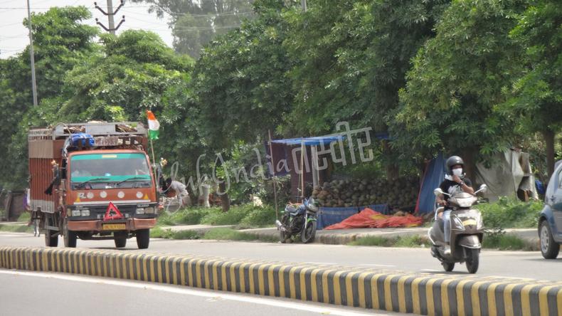 道路を走るオートバイとインド国旗を掲げたトラック