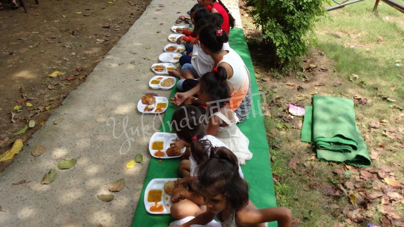 独立記念日の振る舞い料理を地べたに一列に並んで食べるインド人の女の子たち