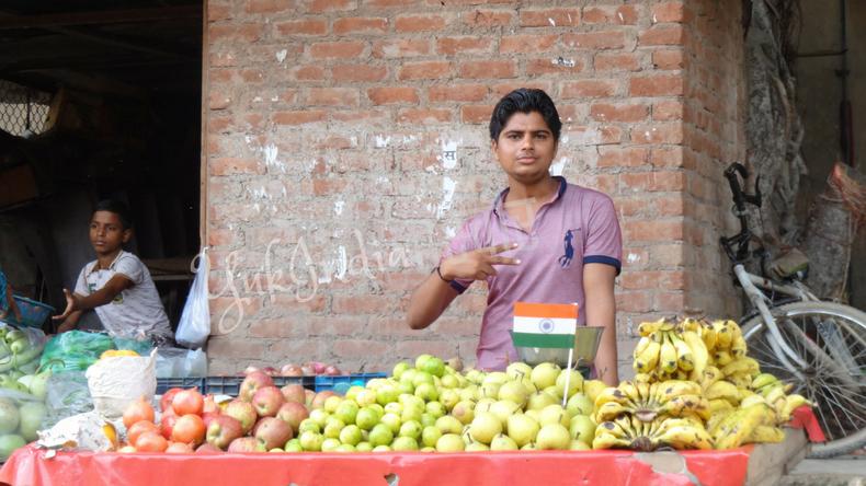 フルーツを山盛りにしたワゴンの後ろでピースサインをするインド人の若者