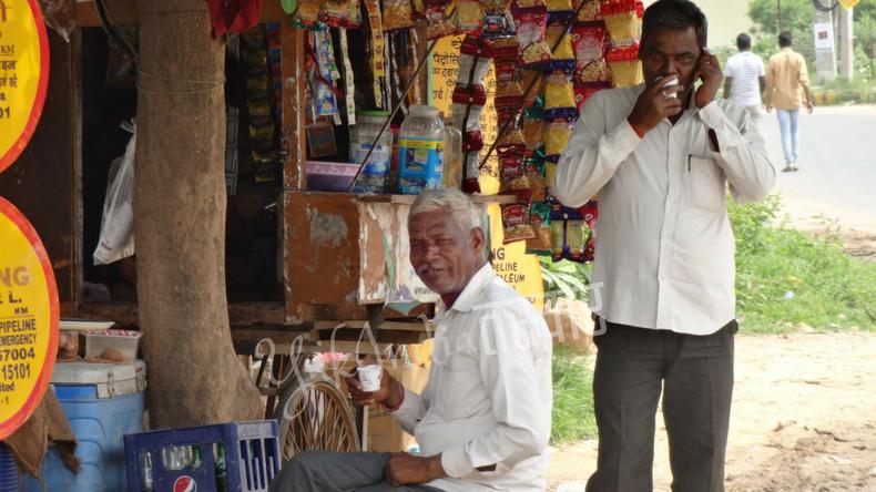 お菓子を売っている店の前でチャイを飲みながら寛ぐインド人男性2人