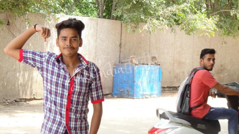 右腕を曲げて筋肉もりもりポーズをするインド人の若者