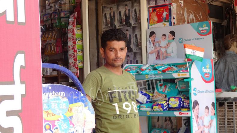 店先でカメラ目線でポーズをとるインド人男性