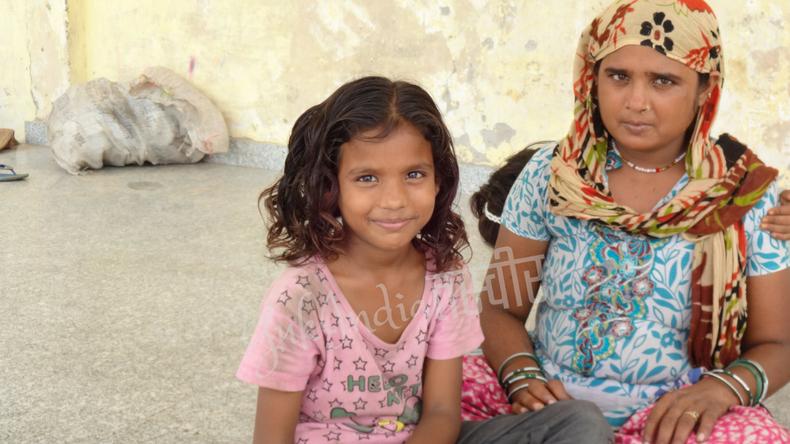 地べたに座り込むインド人母娘がこちらをみて微笑んでいる