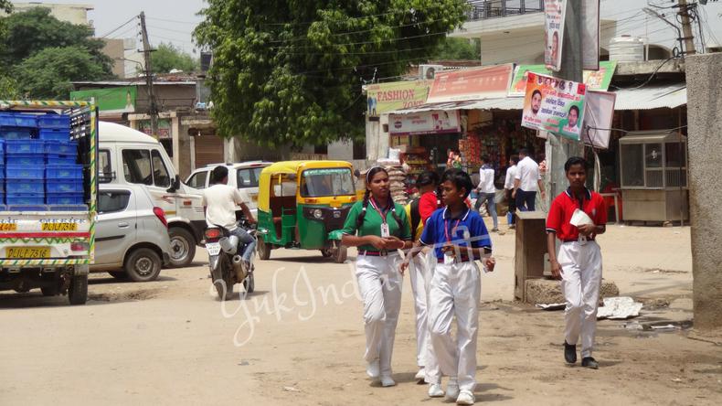 白いパンツにカラフルなポロシャツを着たインド人高校生4人がマーケットを歩く姿