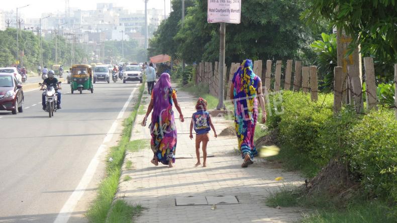 カラフルなサリーの女性二人と小さな子供の後ろ姿