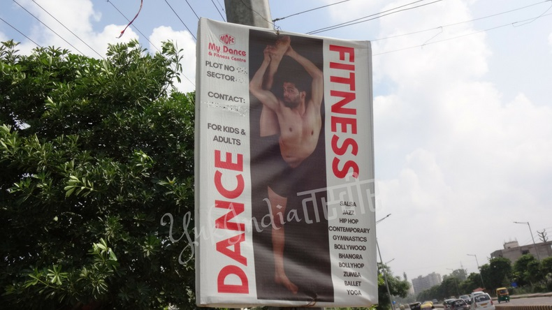 片足を頭の横まで上げた男性の写真がのっているフィットネスとダンスのスタジオの看板