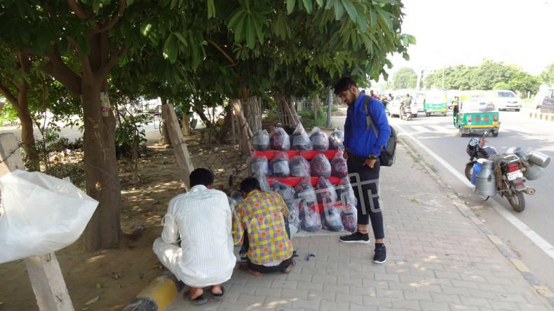 路上にヘルメットを並べている露店と3人のインド人男性