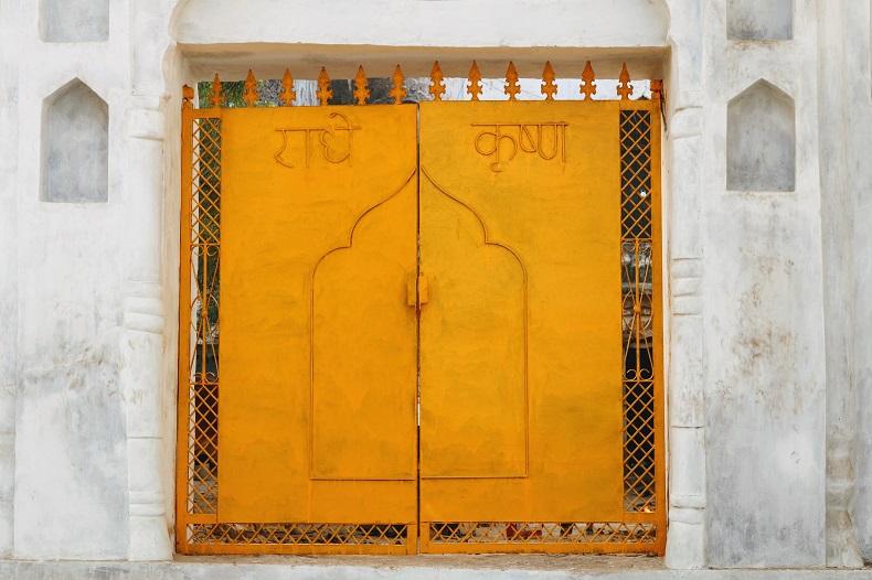 白壁にヒンディ語でなにか書かれた鮮やかな黄色の両開きの扉。お城の扉のようだ。