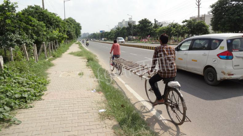 二台の自転車で長梯子を運ぶインド人