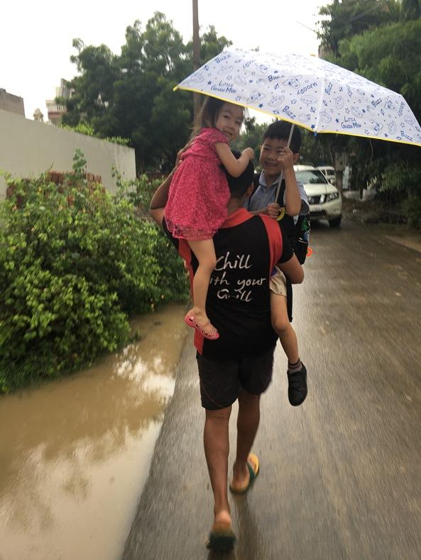 雨の中を子ども2人を肩に担いで歩くインド人男性の後ろ姿