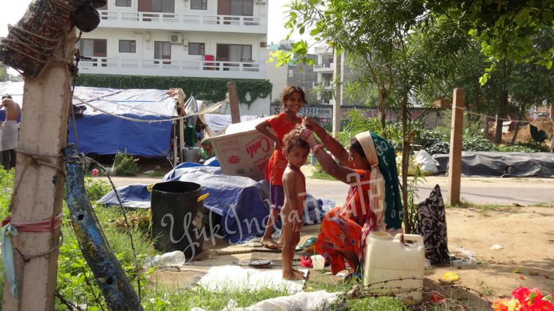 路上で洗われる男の子とその家族