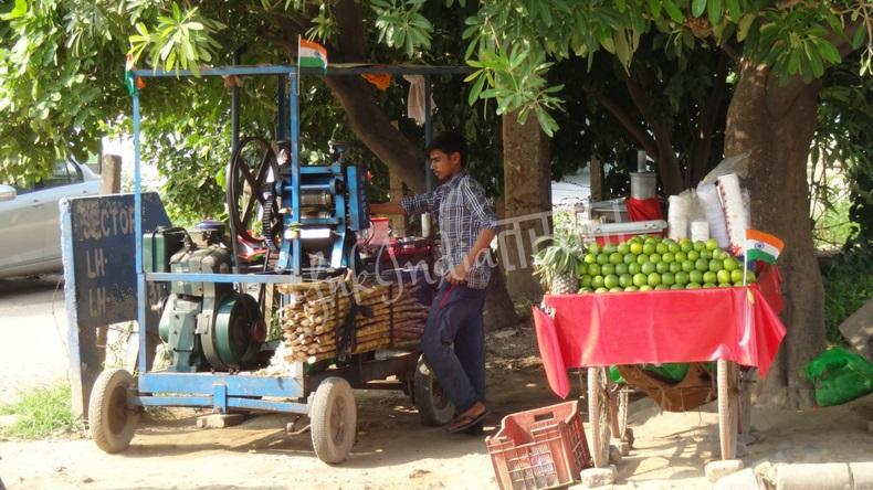 路上で搾りたてのサトウキビやオレンジジュースを売るインド人