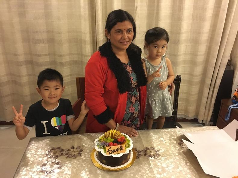 インド人女性と日本人の子ども二人が誕生日ケーキを前に写真を撮っている