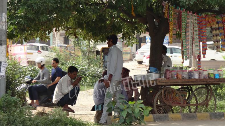 露店のタバコ屋さんの周りで座り込んで寛ぐインド人たち